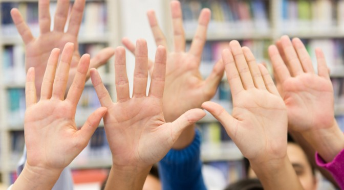 Students raising their hand wanting to participate in class